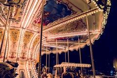 Ιπποδρόμιο παιδιών ` s σε ένα λούνα παρκ στο φωτισμό βραδιού και νύχτας Στοκ Φωτογραφία