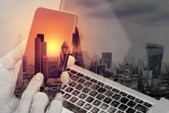 διπλή έκθεση του χεριού που χρησιμοποιεί το έξυπνο τηλέφωνο, lap-top, σε απευθείας σύνδεση τραπεζικές εργασίες Στοκ Εικόνα