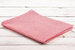 Διπλωμένο κόκκινο ελεγμένο τραπεζομάντιλο στο λευκό ξύλινο πίνακα Στοκ Φωτογραφίες