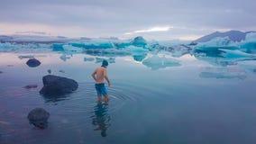 Ισλανδία - νεαρός άνδρας που παίρνει στο νερό της λιμνοθάλασσας παγετώνων στοκ φωτογραφία