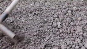 Ισοπέδωση, που χαλαρώνει τη γη στην περιοχή κήπων με τη βοήθεια μιας τσουγκράνας φιλμ μικρού μήκους