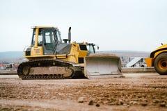 Ισοπεδώνοντας και κινούμενο χώμα μίνι εκσακαφέων εργοτάξιων οικοδομής βιομηχανικού κτηρίου κατά τη διάρκεια του κτηρίου εθνικών ο Στοκ Φωτογραφίες