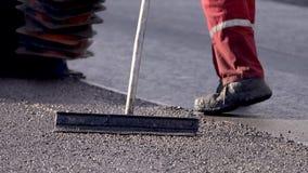 Ισοπεδώνοντας νέο RAD άσφαλτος στο δρόμο Να λειάνει έξω το δρόμο Οι εργαζόμενοι εργάζονται έξω καταυλισμό απόθεμα βίντεο