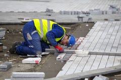 Ισοπεδώνοντας πέτρες επίστρωσης εργαζομένων Στοκ Εικόνες