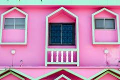 Ισορροπία τριών παραθύρων και balconyof ένα ρόδινο σπίτι Στοκ φωτογραφία με δικαίωμα ελεύθερης χρήσης