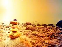 Ισορροπημένη πυραμίδα πετρών στην ακροθαλασσιά, κύματα στο υπόβαθρο ζωηρόχρωμες πέτρες Στοκ φωτογραφία με δικαίωμα ελεύθερης χρήσης