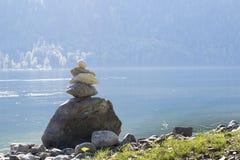 Ισορροπημένη πυραμίδα πετρών στην ακτή του μπλε νερού της λίμνης βουνών στοκ φωτογραφία