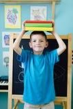 Ισορροπώντας βιβλία σχολικών αγοριών στο κεφάλι του Στοκ εικόνες με δικαίωμα ελεύθερης χρήσης