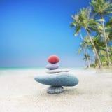 Ισορροπώντας zen πυραμίδα πετρών στην αμμώδη παραλία Στοκ Φωτογραφία