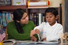 Ισπανικά Mom και αγόρι στο σπίτι-σχολείο που θέτουν τη μελέτη των βράχων Στοκ εικόνες με δικαίωμα ελεύθερης χρήσης