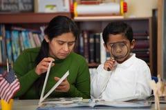 Ισπανικά Mom και αγόρι στο σπίτι-σχολείο που θέτουν τη μελέτη των βράχων Στοκ Εικόνα
