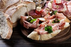 Ισπανικά tapas με το serrano φετών jamon, το σαλάμι, τις ελιές και τους κύβους τυριών σε έναν ξύλινο πίνακα Στοκ Φωτογραφίες