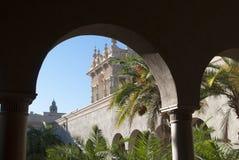 Ισπανική αρχιτεκτονική Άποψη μέσω των αψίδων του παλατιού στον κήπο φοινικών σε μια ηλιόλουστη ημέρα στοκ φωτογραφία