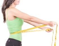 Ισπανική γυναίκα απώλειας βάρους που χαμογελά με τη μέτρηση Στοκ Εικόνα