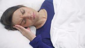 Ισπανική γυναίκα με την πίεση και τον πονοκέφαλο που βρίσκονται στο κρεβάτι απόθεμα βίντεο