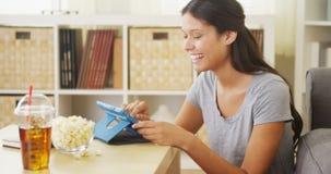 Ισπανική γυναίκα που γελά και που χρησιμοποιεί την ταμπλέτα στο τραπεζάκι σαλονιού Στοκ Εικόνες
