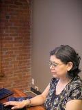 Ισπανική γυναίκα που χρησιμοποιεί τον υπολογιστή στην εργασία Στοκ Εικόνες