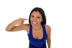 Ισπανική γυναίκα στην περιστασιακή κορυφή και τζιν που χαμογελούν το ευτυχή και εύθυμα στόμα και τα δόντια υπόδειξης στοκ εικόνα