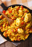 Ισπανική κουζίνα: Στενός επάνω pollo Arroz con σε ένα τηγάνι Κατακόρυφος Στοκ Εικόνες