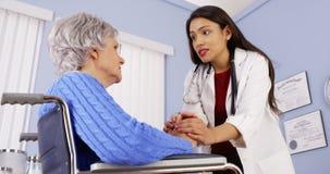 Ισπανικός γιατρός γυναικών που ανακουφίζει το με ειδικές ανάγκες ηλικιωμένο ασθενή στοκ εικόνα