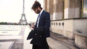 Ισπανικός επιχειρηματίας που καλεί το συνεργάτη με το τηλέφωνο κοντά στον πύργο του Άιφελ σε σε αργή κίνηση φιλμ μικρού μήκους
