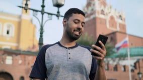 Ισπανικός τουρίστας που εξετάζει το τηλέφωνό του που στέκεται κοντά στη Μόσχα Κρεμλίνο το καλοκαίρι απόθεμα βίντεο