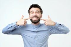 Ισπανικό άτομο που χαμογελά τη βέβαια παρουσίαση και που δείχνει με τα δόντια και το στόμα δάχτυλων στοκ εικόνες
