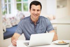 Ισπανικό άτομο που χρησιμοποιεί το lap-top στην κουζίνα στο σπίτι Στοκ φωτογραφία με δικαίωμα ελεύθερης χρήσης