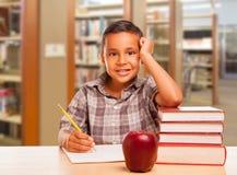 Ισπανικό αγόρι με τα βιβλία, Apple, μολύβι και έγγραφο στη βιβλιοθήκη Στοκ εικόνες με δικαίωμα ελεύθερης χρήσης