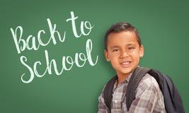 Ισπανικό αγόρι μπροστά από πίσω στον πίνακα σχολικής κιμωλίας Στοκ Εικόνες