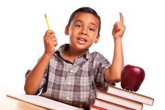 Ισπανικό αγόρι που αυξάνει το χέρι, τα βιβλία του, τη Apple, το μολύβι και το έγγραφο Στοκ φωτογραφία με δικαίωμα ελεύθερης χρήσης