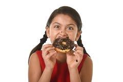 Ισπανικό κορίτσι στο κόκκινο φόρεμα που τρώει doughnut σοκολάτας με τα χέρια και το στόμα που λεκιάζουν και το βρώμικο χαμόγελο ε Στοκ Εικόνες