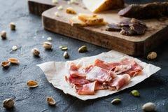 Ισπανικό serrano ζαμπόν jamon ή toscano pecorino ιταλικό crudo prosciutto με το τεμαχισμένο ιταλικό σκληρών τυριών, σπιτικό ξηρό  Στοκ Εικόνα