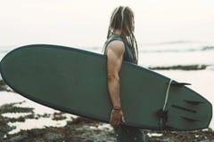 Ιστιοσανίδα εκμετάλλευσης μυών surfer, που φαίνεται ο ωκεανός στοκ φωτογραφία
