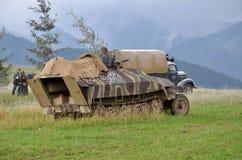 Ιστορική αναπαράσταση του παγκόσμιου πολέμου 2 μάχη - το θωρακισμένοι όχημα μεταφορών και οι στρατιώτες έντυσαν στις γερμανικές ν στοκ εικόνες με δικαίωμα ελεύθερης χρήσης