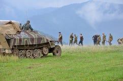 Ιστορική αναπαράσταση του παγκόσμιου πολέμου 2 μάχη - το θωρακισμένοι όχημα μεταφορών και οι στρατιώτες έντυσαν στις γερμανικές ν Στοκ εικόνα με δικαίωμα ελεύθερης χρήσης