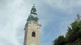 Ιστορικός πύργος με τα ρολόγια και το θόλο χαλκού της καθολικής εκκλησίας ενάντια στον ουρανό το καλοκαίρι φιλμ μικρού μήκους