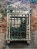 Ιστορικό παράθυρο που ανοίγει με τους φραγμούς στο αρχαίο ρωμαϊκό σπίτι Στοκ Φωτογραφίες