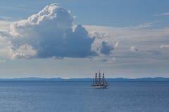 Ιστορικό πλέοντας σκάφος κάτω από την μπλε θάλασσα και τον ουρανό σύννεφων Στοκ Εικόνα