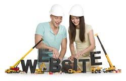 Ιστοχώρος κάτω από την κατασκευή: Χαρούμενοι άνδρας και γυναίκα που χτίζουν websit Στοκ Φωτογραφίες