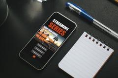 Ιστοχώρος app τηλεοπτικής σειράς σε μια κινητή τηλεφωνική οθόνη, που τοποθετείται σε ένα μαύρο γραφείο Στοκ Εικόνα