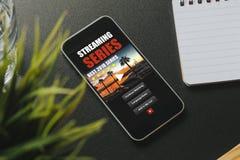 Ιστοχώρος app τηλεοπτικής σειράς σε μια κινητή τηλεφωνική οθόνη, που τοποθετείται σε ένα μαύρο γραφείο Στοκ Εικόνες