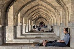 ΙΣΦΑΧΑΝ, ΙΡΑΝ - 20 ΑΥΓΟΎΣΤΟΥ 2016: Ιρανικοί λαοί που στηρίζονται κάτω από τις αψίδες της γέφυρας Khaju, στο Ισφαχάν, στις θερμότε στοκ εικόνες