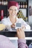 Ισχυρά κτυπήματα πελατών η πιστωτική κάρτα του για να κάνει την πληρωμή Στοκ Εικόνα