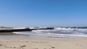 Ισχυρά κύματα θάλασσας που χτυπούν ενάντια στην αποβάθρα και την αμμώδη παραλία μια ηλιόλουστη θυελλώδη ημέρα Θυελλώδης καιρός πα απόθεμα βίντεο