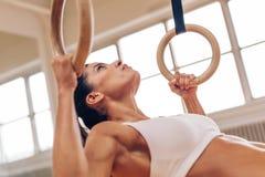 Ισχυρή γυναίκα που κάνει το τράβηγμα-UPS με τα γυμναστικά δαχτυλίδια Στοκ Εικόνες
