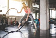 Ισχυρή γυναίκα που χρησιμοποιεί το σχοινί μάχης στη γυμναστική, θηλυκή να κάνει άσκηση στη λειτουργική κατάρτιση στοκ φωτογραφία