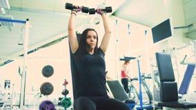 Ισχυρή γυναίκα brunette που κάνει την άσκηση στη λέσχη ικανότητας απόθεμα βίντεο