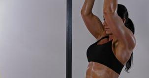 Ισχυρή κατάλληλη καυκάσια γυναίκα που κάνει το τράβηγμα UPS σε μια γυμναστική απόθεμα βίντεο