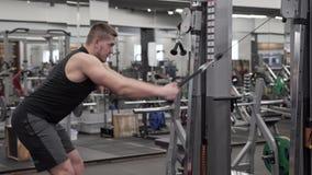 Ισχυρή νέα αρσενική ενήλικη να κάνει άσκηση προσομοιωτών για τους μυς πλατών και όπλων φιλμ μικρού μήκους